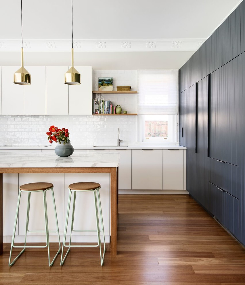 Large trendy dark wood floor open concept kitchen photo in Sydney with flat-panel cabinets, gray cabinets, marble countertops, white backsplash, ceramic backsplash, stainless steel appliances and an island