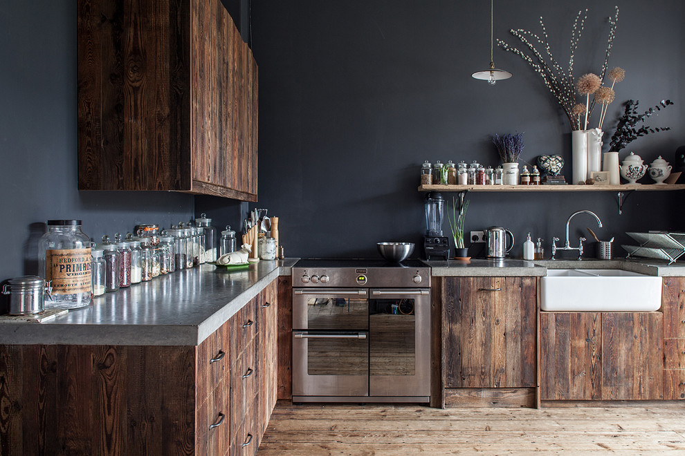 Inspiration for a large rustic l-shaped enclosed kitchen in London with a belfast sink, flat-panel cabinets, dark wood cabinets and concrete worktops.
