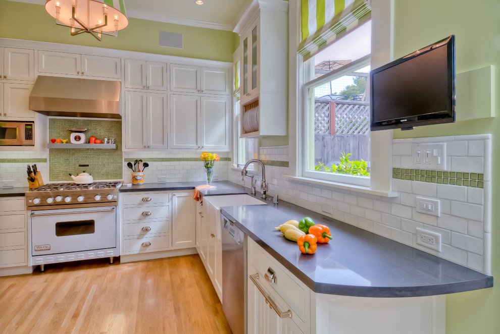 Example of a trendy l-shaped kitchen design in San Francisco with white appliances, a farmhouse sink, quartz countertops, shaker cabinets, white cabinets, green backsplash and subway tile backsplash
