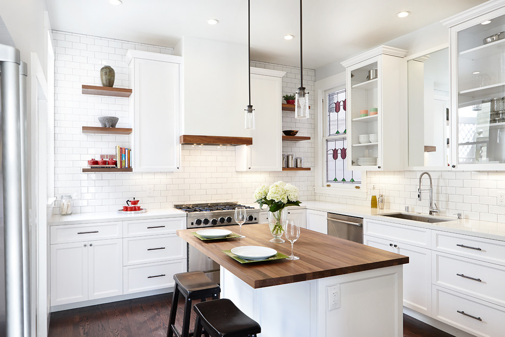 Inspiration for a mid-sized timeless l-shaped dark wood floor kitchen remodel in San Francisco with a single-bowl sink, recessed-panel cabinets, white cabinets, quartz countertops, white backsplash, subway tile backsplash, stainless steel appliances and an island