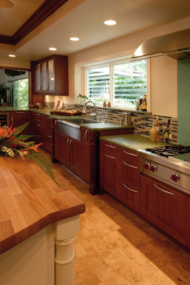 Inspiration for a tropical cork floor eat-in kitchen remodel in Hawaii with a farmhouse sink, wood countertops, glass tile backsplash, stainless steel appliances, shaker cabinets, medium tone wood cabinets, multicolored backsplash and green countertops