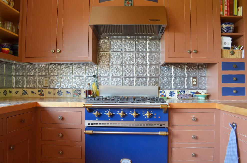 Inspiration for a rustic kitchen remodel in Boise with metal backsplash, colored appliances, tile countertops, metallic backsplash and shaker cabinets