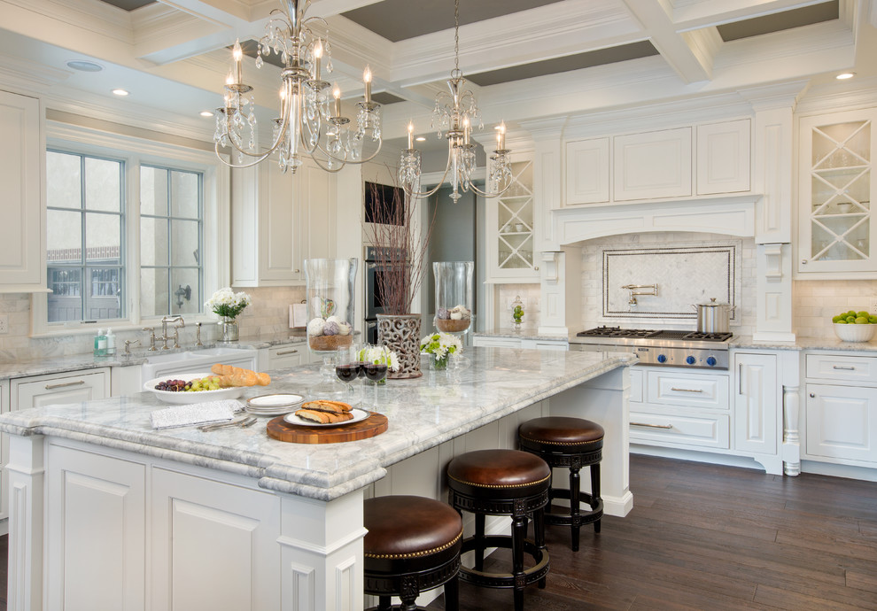 Kitchen - large traditional l-shaped dark wood floor kitchen idea in Columbus with a farmhouse sink, white cabinets, granite countertops, an island, raised-panel cabinets, white backsplash and stainless steel appliances