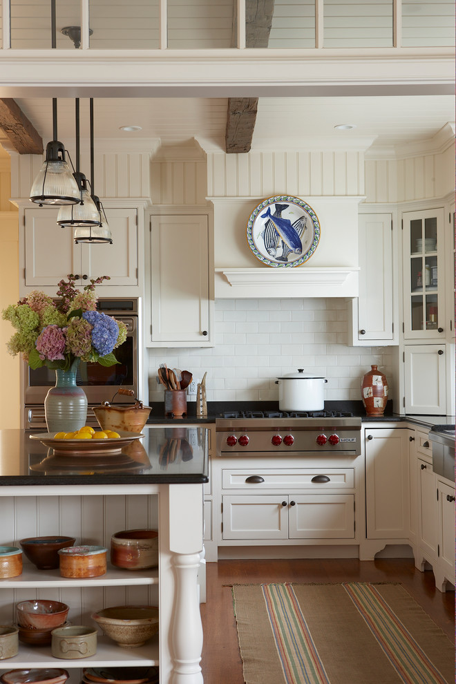 Eat-in kitchen - traditional u-shaped eat-in kitchen idea in Boston with stainless steel appliances, granite countertops, a farmhouse sink, recessed-panel cabinets, white cabinets, white backsplash and subway tile backsplash
