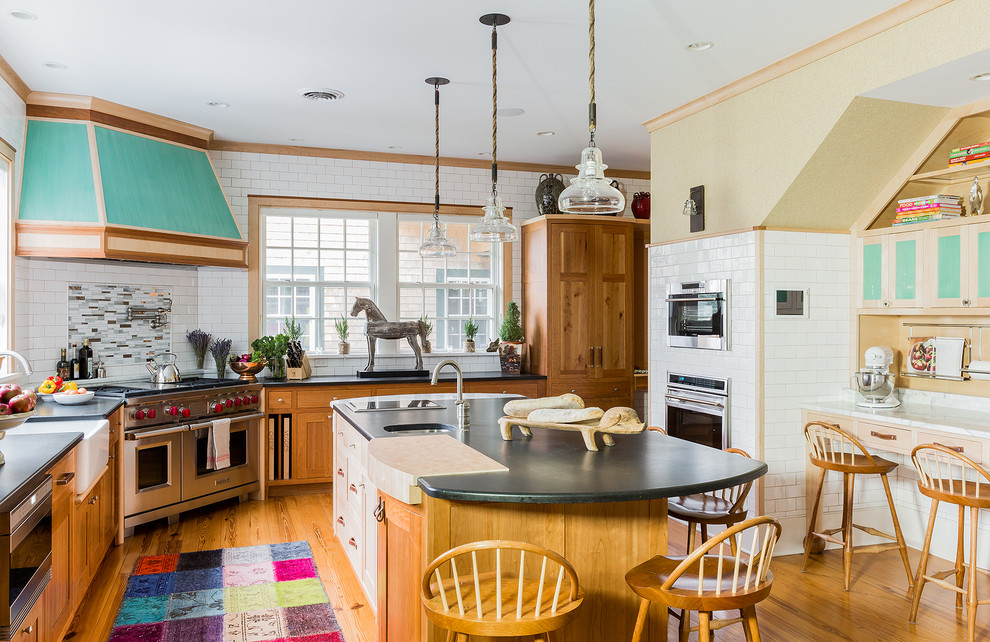 Example of a large classic l-shaped medium tone wood floor and brown floor kitchen design in Boston with an island, a farmhouse sink, shaker cabinets, light wood cabinets, white backsplash, subway tile backsplash, stainless steel appliances and granite countertops