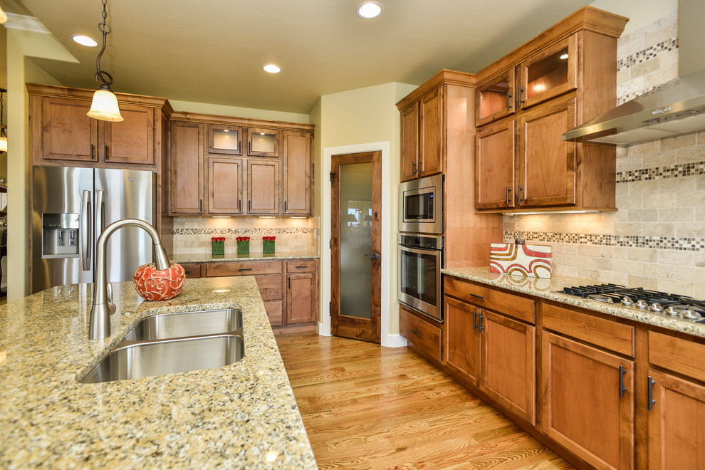Elegant kitchen photo in Denver with recessed-panel cabinets and medium tone wood cabinets