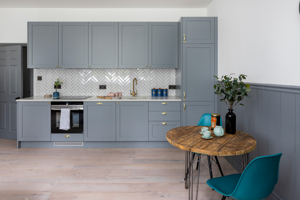 Example of a small trendy single-wall medium tone wood floor and beige floor eat-in kitchen design in Hertfordshire with an undermount sink, shaker cabinets, gray cabinets, quartzite countertops, white backsplash, black appliances, no island and white countertops
