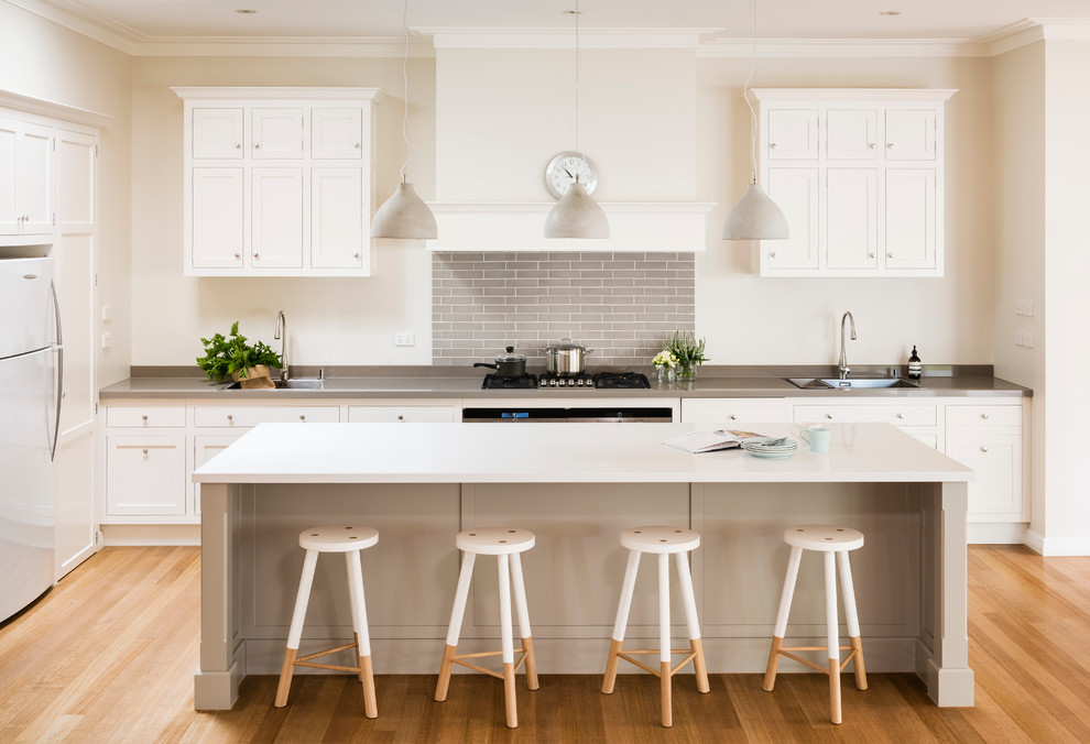 Inspiration for a transitional medium tone wood floor kitchen remodel in Melbourne with a drop-in sink, shaker cabinets, white cabinets, white appliances, an island, gray backsplash and subway tile backsplash