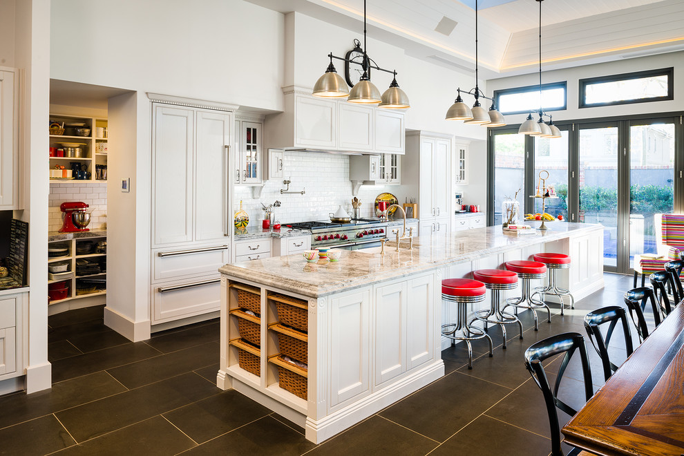Kitchen - huge traditional porcelain tile and gray floor kitchen idea in Melbourne with a farmhouse sink, white cabinets, granite countertops, white backsplash, an island, subway tile backsplash, shaker cabinets, stainless steel appliances and multicolored countertops