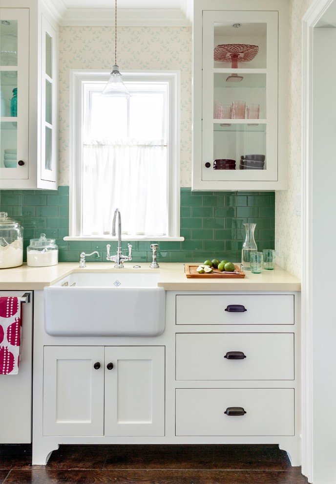 Small beach style single-wall dark wood floor kitchen photo in Los Angeles with a farmhouse sink, recessed-panel cabinets, white cabinets, quartz countertops, green backsplash and glass tile backsplash