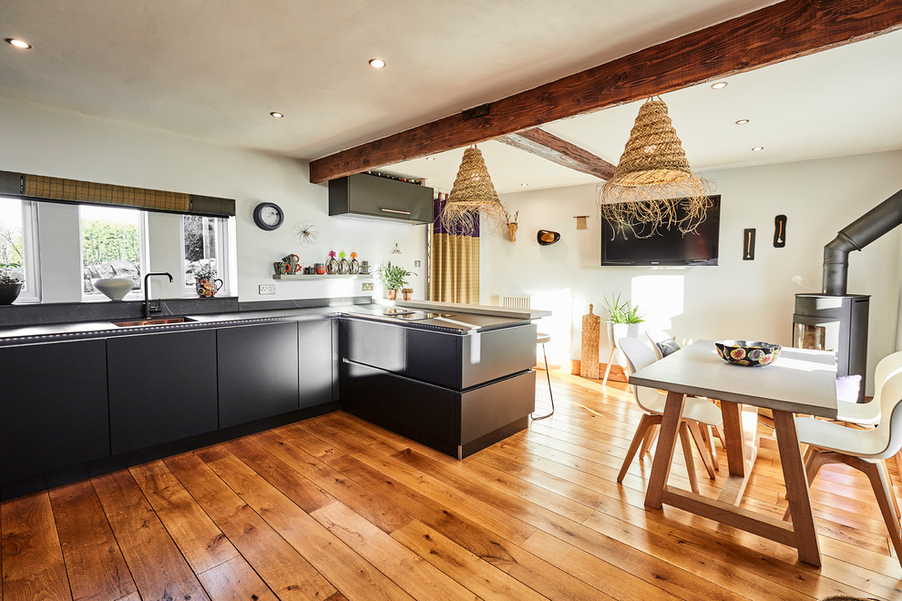 Inspiration for a mid-sized modern u-shaped dark wood floor and beige floor eat-in kitchen remodel in Other with a drop-in sink, flat-panel cabinets, black cabinets, quartz countertops, black backsplash, black appliances, a peninsula and black countertops