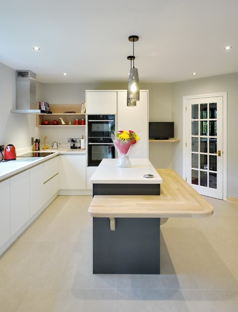 This is an example of a mid-sized contemporary l-shaped kitchen in Other with flat-panel cabinets, white cabinets, an island and beige floor.