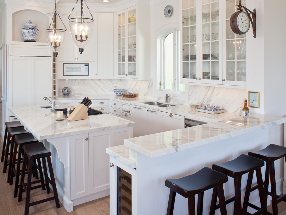 Mid-sized elegant u-shaped light wood floor and brown floor eat-in kitchen photo in Tampa with glass-front cabinets, an undermount sink, white cabinets, marble countertops, white backsplash, marble backsplash, paneled appliances and an island