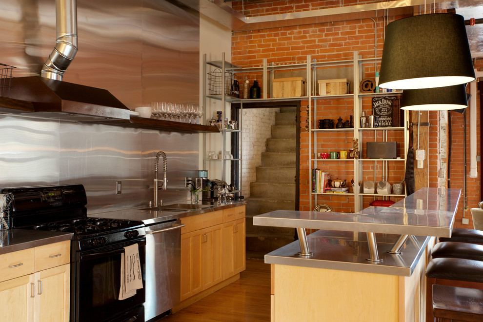 Urban galley open concept kitchen photo in Edmonton with light wood cabinets, stainless steel countertops, metal backsplash, black appliances and an island
