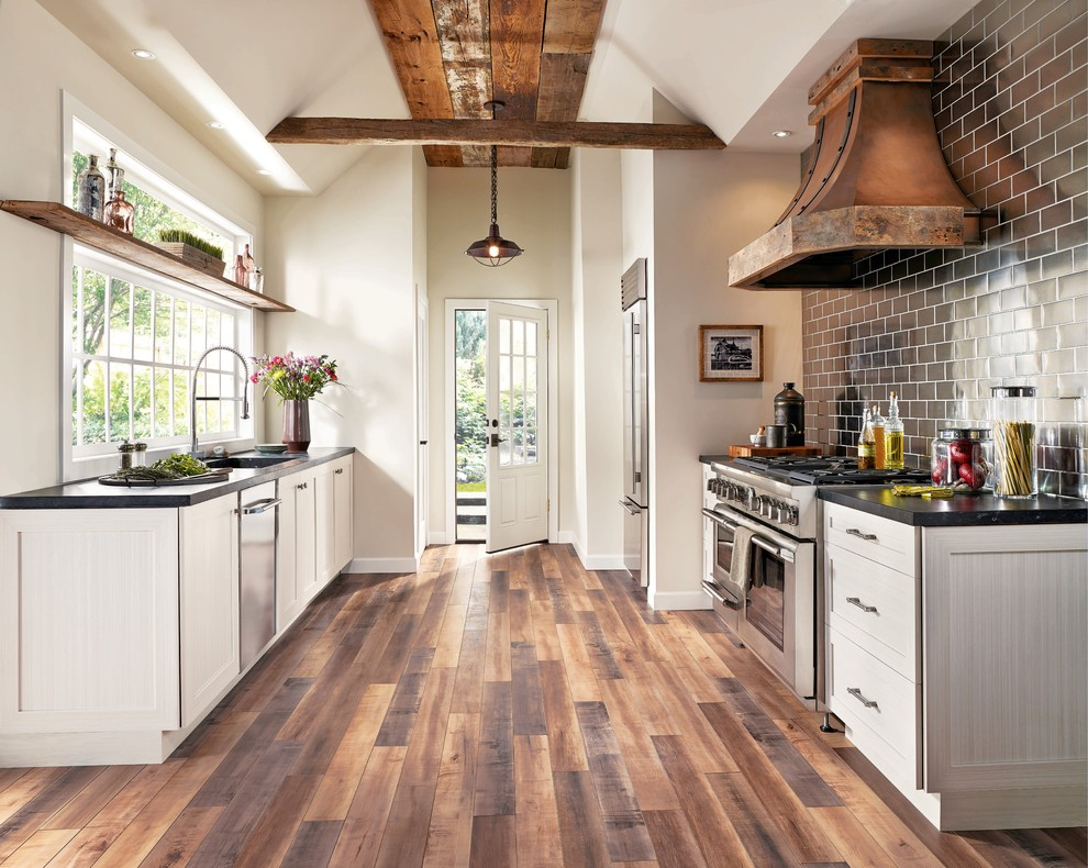Mid-sized country galley dark wood floor and brown floor eat-in kitchen photo in San Diego with shaker cabinets, white cabinets, black backsplash, subway tile backsplash, stainless steel appliances, no island, an undermount sink and soapstone countertops