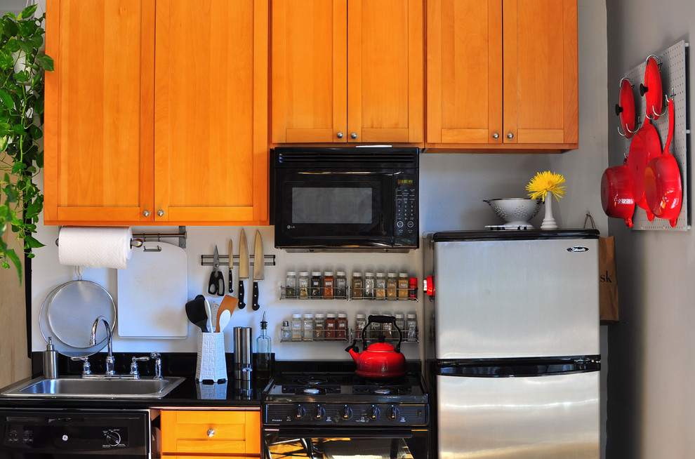 Example of an eclectic single-wall kitchen design in New York with a drop-in sink, shaker cabinets, medium tone wood cabinets and black appliances
