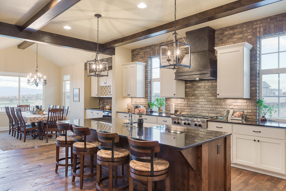 Example of a mid-sized farmhouse galley medium tone wood floor eat-in kitchen design in Denver with recessed-panel cabinets, white cabinets, quartzite countertops, brown backsplash, stainless steel appliances, an island and stone tile backsplash