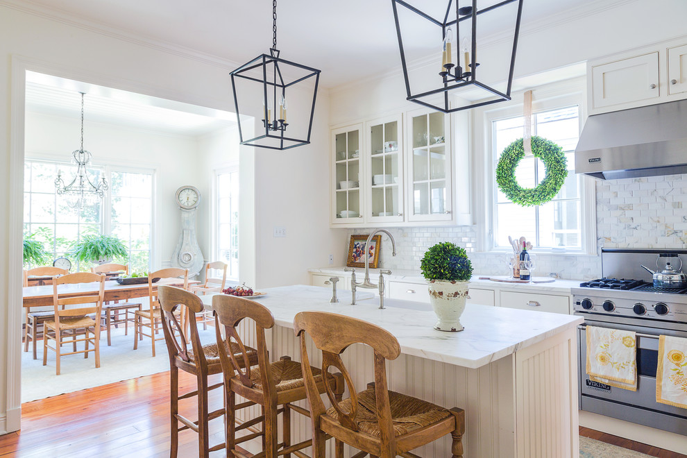 Inspiration for a mid-sized timeless l-shaped medium tone wood floor and brown floor kitchen remodel in New Orleans with glass-front cabinets, white cabinets, multicolored backsplash, stainless steel appliances, an island and a farmhouse sink