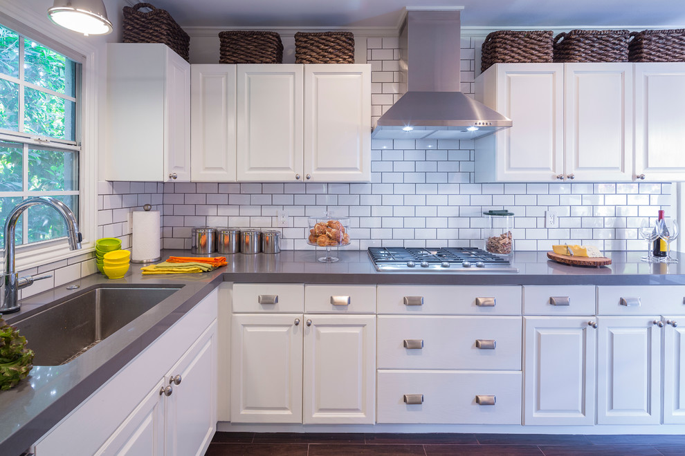 Example of a transitional enclosed kitchen design in Los Angeles with an undermount sink, recessed-panel cabinets, white cabinets, white backsplash, subway tile backsplash, stainless steel appliances and no island
