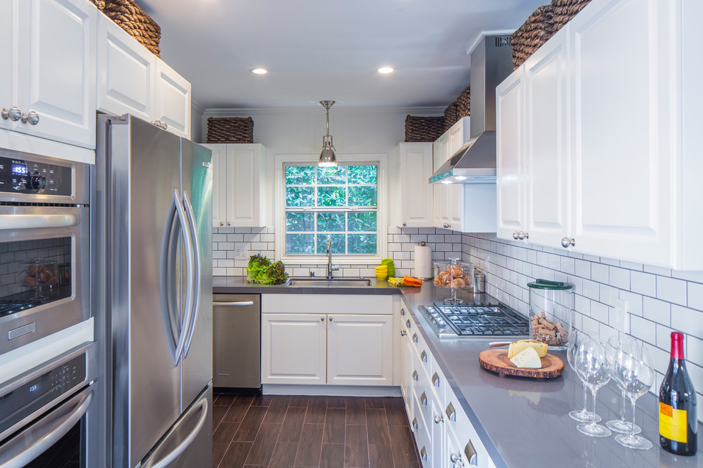 Example of a transitional u-shaped dark wood floor kitchen design in Los Angeles with an undermount sink, raised-panel cabinets, white cabinets, white backsplash and subway tile backsplash