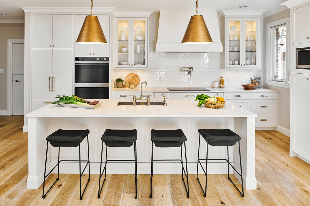 Example of a mid-sized transitional light wood floor and beige floor kitchen design in Vancouver with white cabinets, quartz countertops, white backsplash, stainless steel appliances, an island, white countertops, an undermount sink, glass-front cabinets and subway tile backsplash