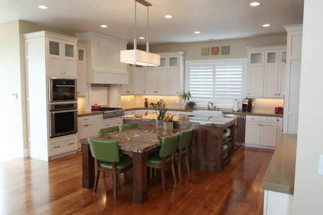 Example of a mid-sized classic u-shaped medium tone wood floor open concept kitchen design in Salt Lake City with a farmhouse sink, white cabinets, white backsplash, subway tile backsplash, stainless steel appliances, shaker cabinets, granite countertops and an island