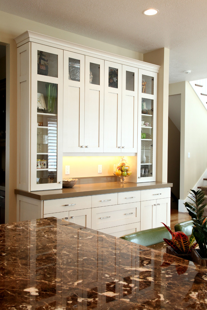 Mid-sized elegant u-shaped medium tone wood floor open concept kitchen photo in Salt Lake City with a farmhouse sink, shaker cabinets, white cabinets, granite countertops, white backsplash, subway tile backsplash, stainless steel appliances and an island