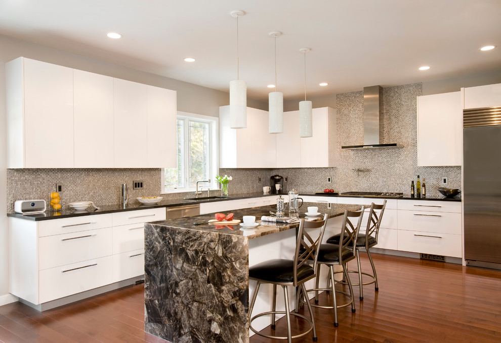 Inspiration for a large contemporary u-shaped medium tone wood floor kitchen remodel in Boston with mosaic tile backsplash, stainless steel appliances, flat-panel cabinets, white cabinets, an island, an undermount sink, quartz countertops and gray backsplash