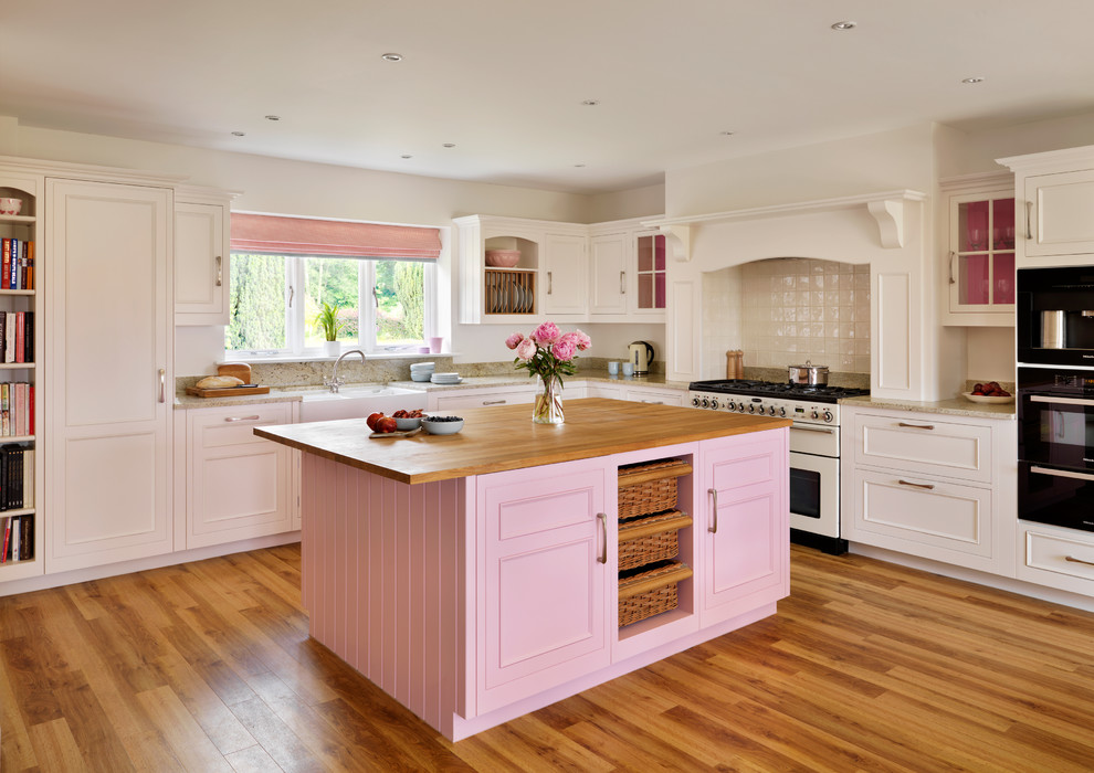 Example of a farmhouse l-shaped kitchen design in London with white appliances and an island