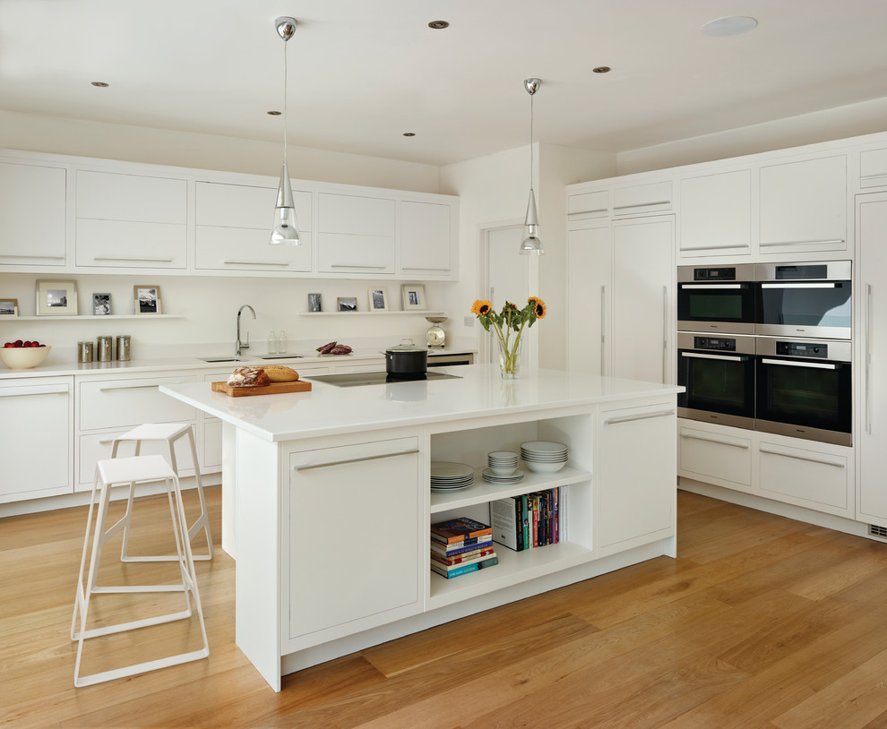 Large danish l-shaped medium tone wood floor kitchen photo in London with an undermount sink, flat-panel cabinets, white cabinets, white backsplash, paneled appliances and an island