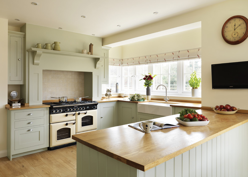 Example of a classic u-shaped kitchen design in London with a farmhouse sink, green cabinets and a peninsula