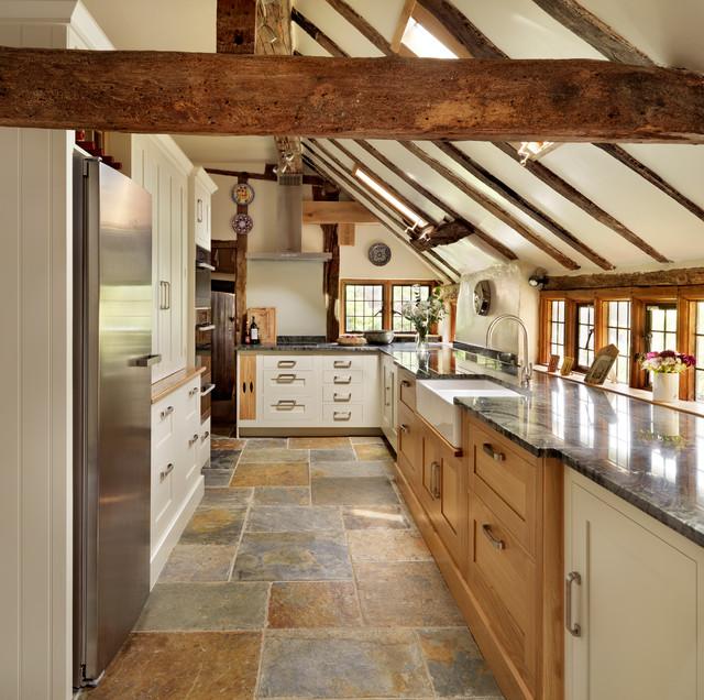 Réalisation d'une cuisine champêtre en U de taille moyenne avec un évier de ferme, un placard à porte shaker, des portes de placard blanches et un électroménager en acier inoxydable.