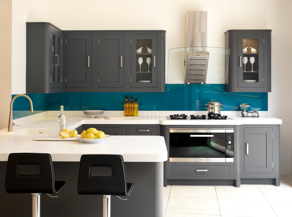 Inspiration for a transitional u-shaped kitchen remodel in London with an integrated sink, shaker cabinets, gray cabinets, blue backsplash, glass sheet backsplash, stainless steel appliances and a peninsula