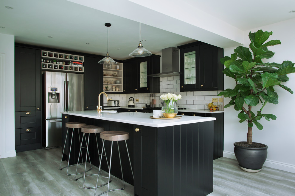 Inspiration for a large contemporary ceramic floor and gray floor eat-in kitchen remodel in London with a farmhouse sink, recessed-panel cabinets, black cabinets, quartzite countertops, white backsplash, stainless steel appliances and an island