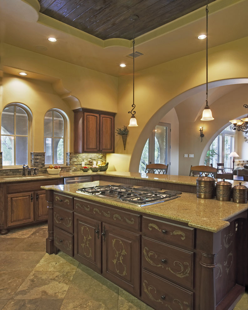 Example of a tuscan kitchen design in Austin with raised-panel cabinets, dark wood cabinets and gray backsplash