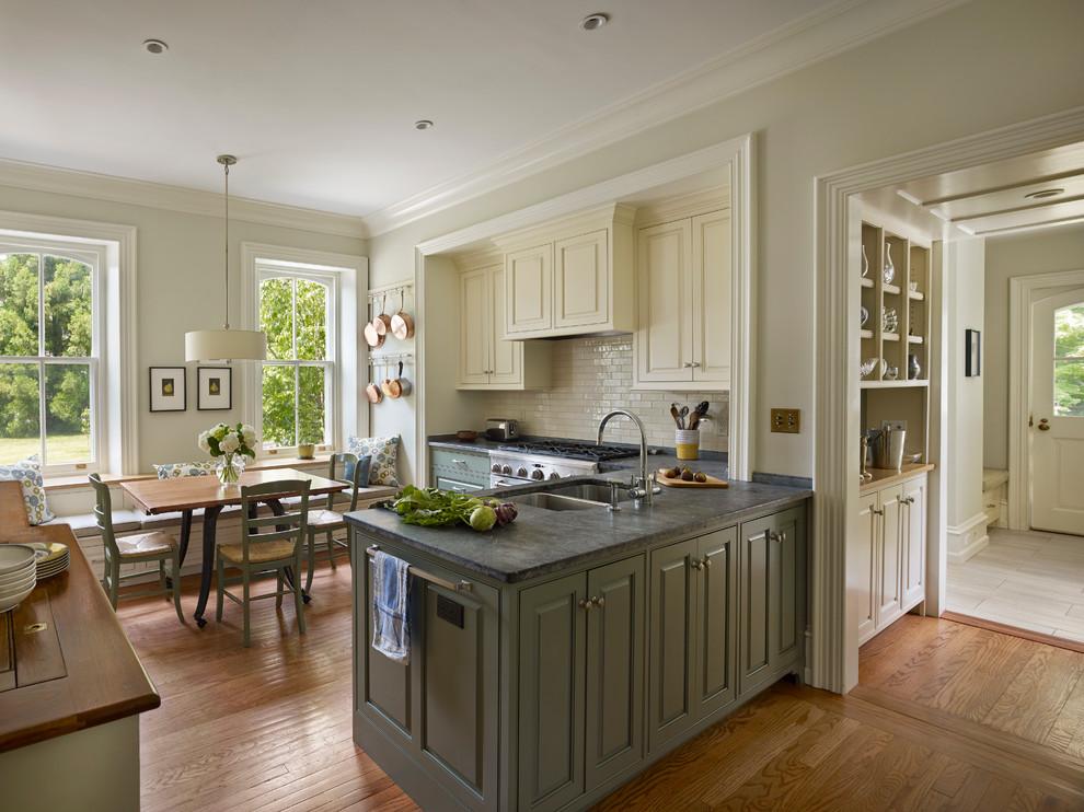Elegant eat-in kitchen photo in Philadelphia with a double-bowl sink, soapstone countertops, white backsplash, subway tile backsplash, raised-panel cabinets and green cabinets