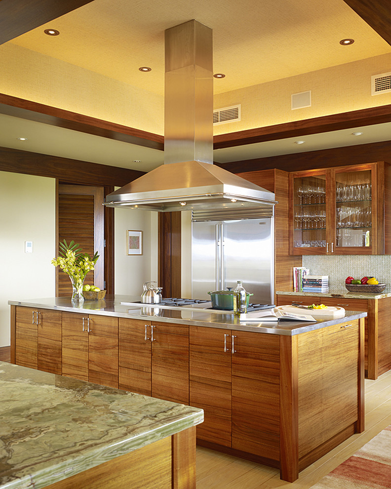 Example of an island style kitchen design in Hawaii with flat-panel cabinets and stainless steel appliances
