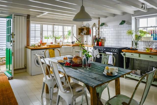 Idee per una cucina boho chic di medie dimensioni con lavello stile country, ante in stile shaker, ante verdi, top in legno, paraspruzzi bianco, paraspruzzi con piastrelle in ceramica, elettrodomestici neri, pavimento in legno verniciato e pavimento bianco