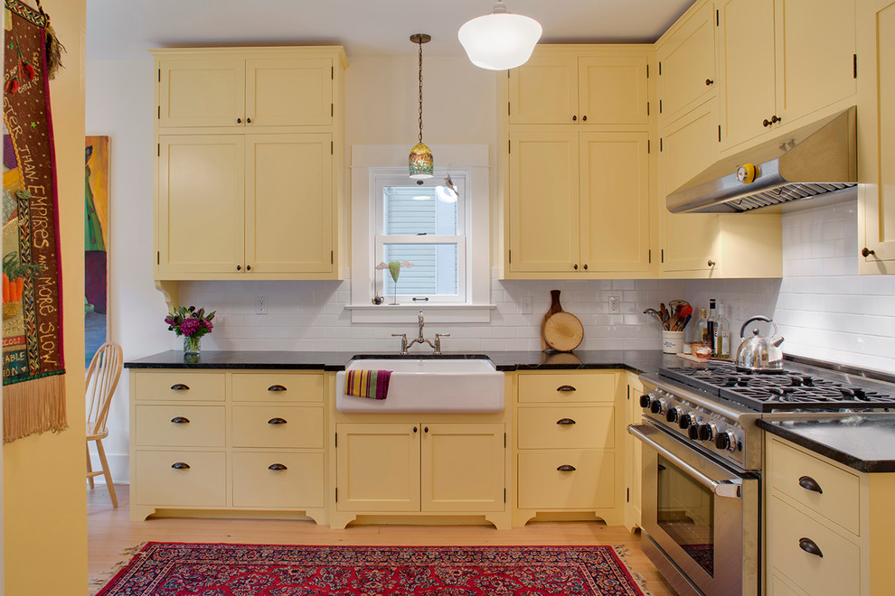 Elegant kitchen photo in Portland with subway tile backsplash, a farmhouse sink, shaker cabinets, yellow cabinets, white backsplash, soapstone countertops and stainless steel appliances