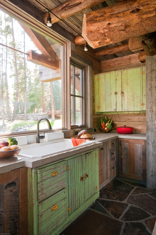 Mountain style kitchen photo in Other with concrete countertops, a drop-in sink and distressed cabinets
