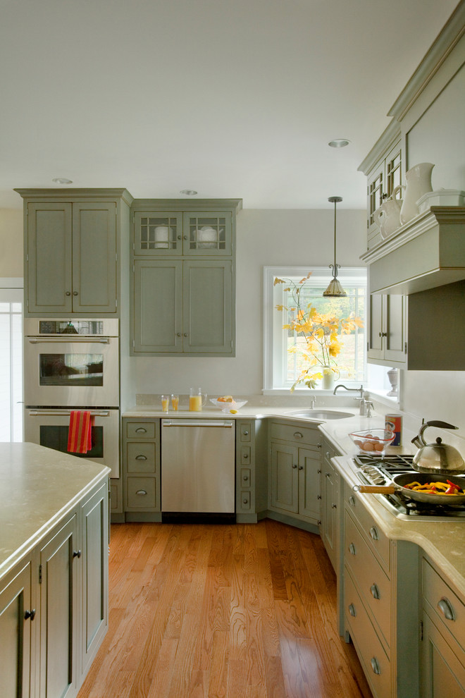 Inspiration for a mid-sized timeless l-shaped medium tone wood floor eat-in kitchen remodel in Boston with recessed-panel cabinets, green cabinets and stainless steel appliances