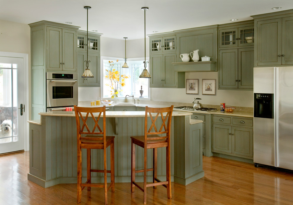 Example of a mid-sized classic l-shaped medium tone wood floor eat-in kitchen design in Boston with recessed-panel cabinets, green cabinets and stainless steel appliances