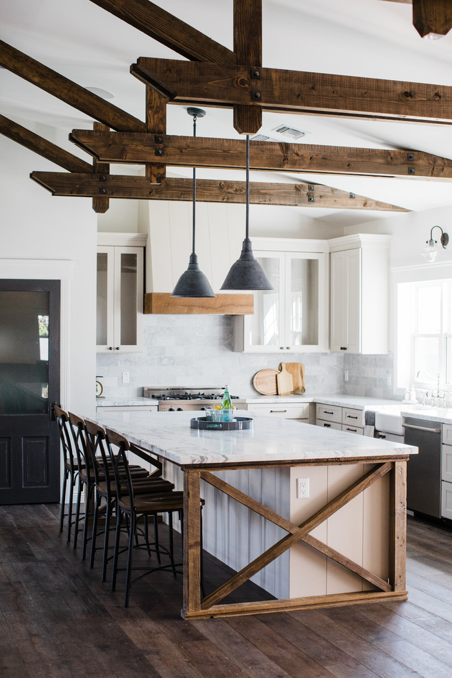 Example of a country l-shaped dark wood floor and brown floor kitchen design in Phoenix with a farmhouse sink, recessed-panel cabinets, white cabinets, gray backsplash, stainless steel appliances and an island