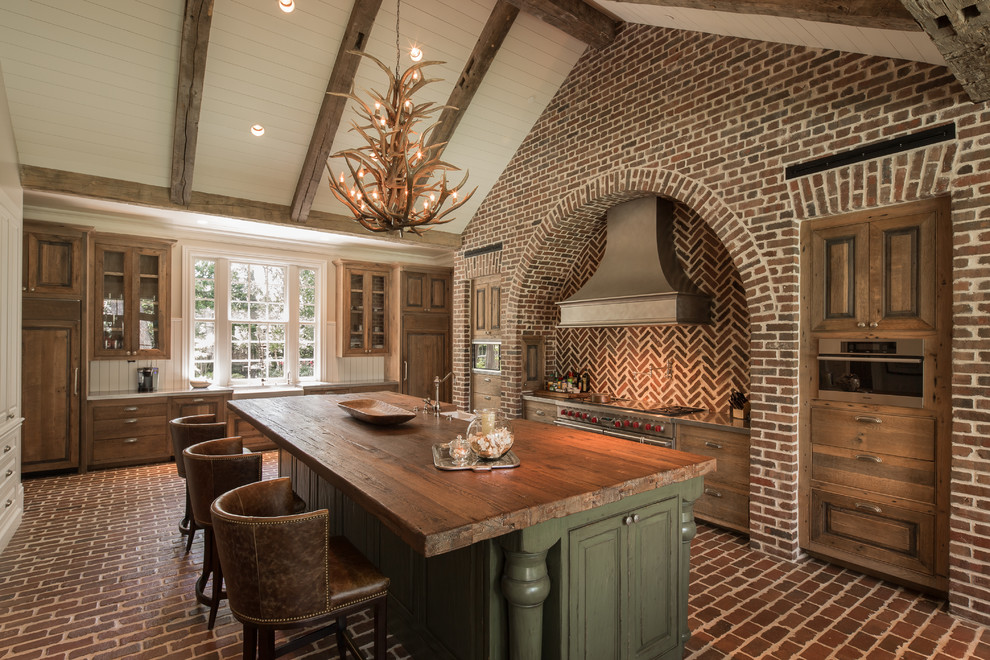 Inspiration for a rustic brick floor kitchen remodel in Houston with a farmhouse sink, medium tone wood cabinets, stainless steel countertops, stainless steel appliances and an island
