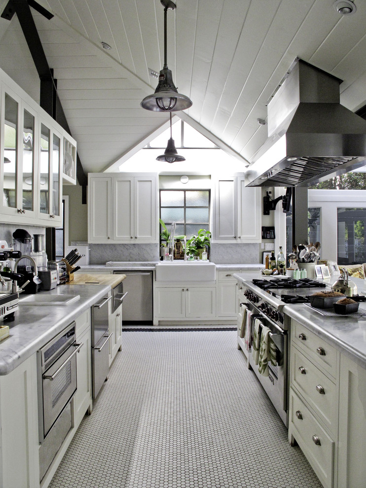 Example of a classic kitchen design in Los Angeles with glass-front cabinets, a farmhouse sink and stainless steel appliances