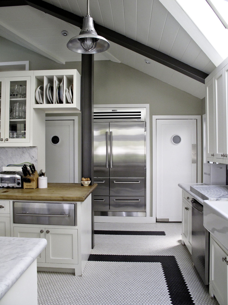Kitchen - traditional kitchen idea in Los Angeles with glass-front cabinets and a farmhouse sink