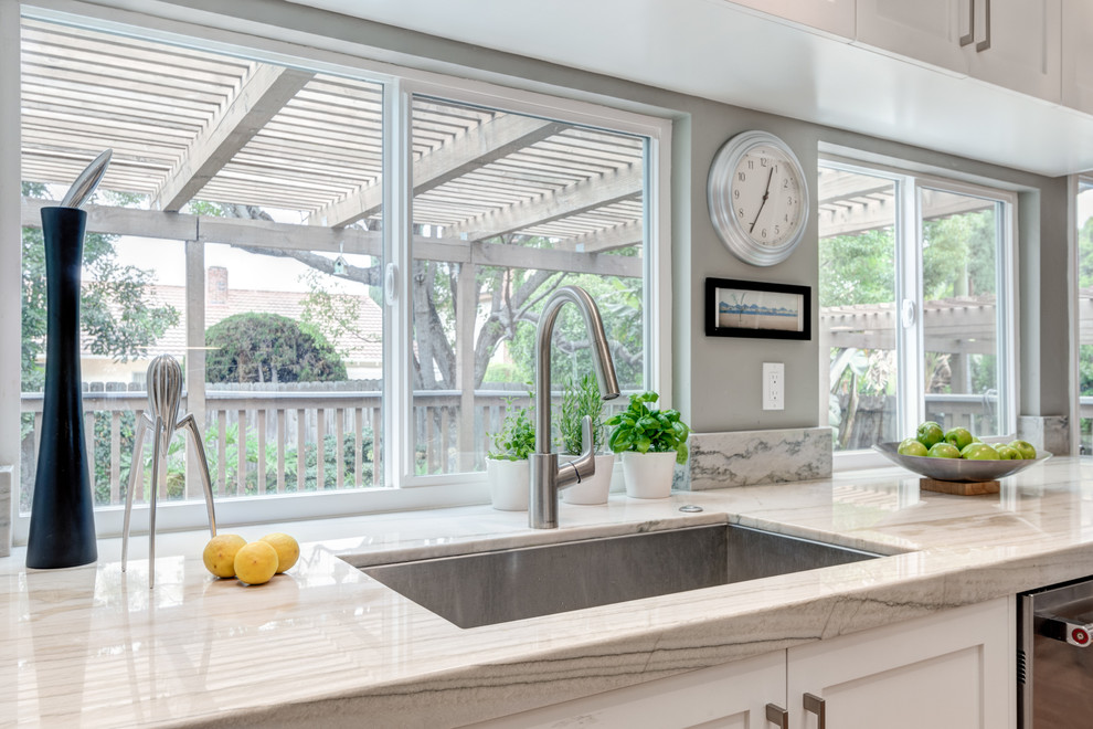 Example of a mid-sized transitional galley medium tone wood floor eat-in kitchen design in San Diego with an undermount sink, shaker cabinets, white cabinets, quartzite countertops, blue backsplash, porcelain backsplash, stainless steel appliances and no island