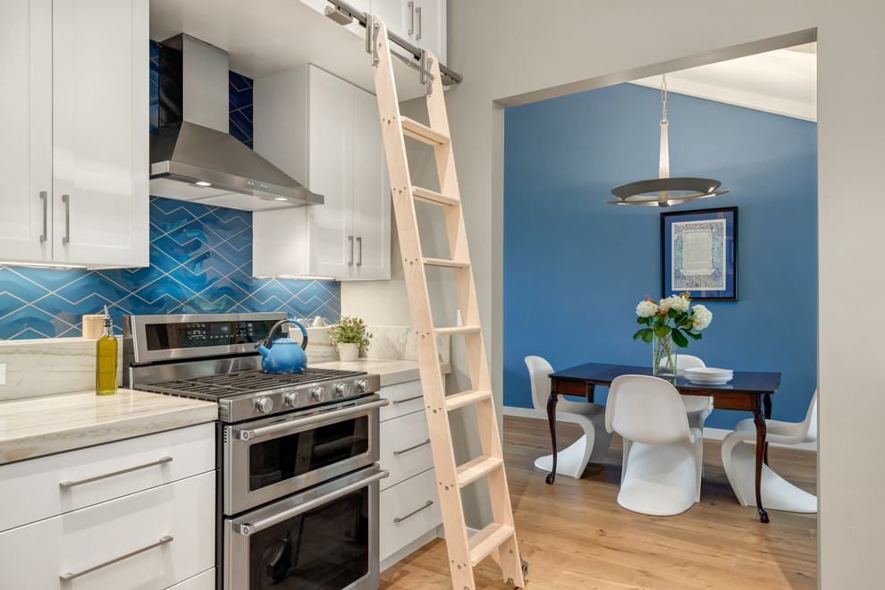 Mid-sized transitional galley medium tone wood floor eat-in kitchen photo in San Diego with an undermount sink, shaker cabinets, white cabinets, quartzite countertops, blue backsplash, porcelain backsplash, stainless steel appliances and no island