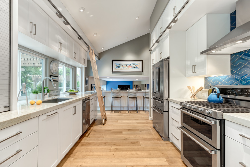 Inspiration for a mid-sized transitional galley medium tone wood floor eat-in kitchen remodel in San Diego with an undermount sink, shaker cabinets, white cabinets, quartzite countertops, blue backsplash, porcelain backsplash, stainless steel appliances and no island