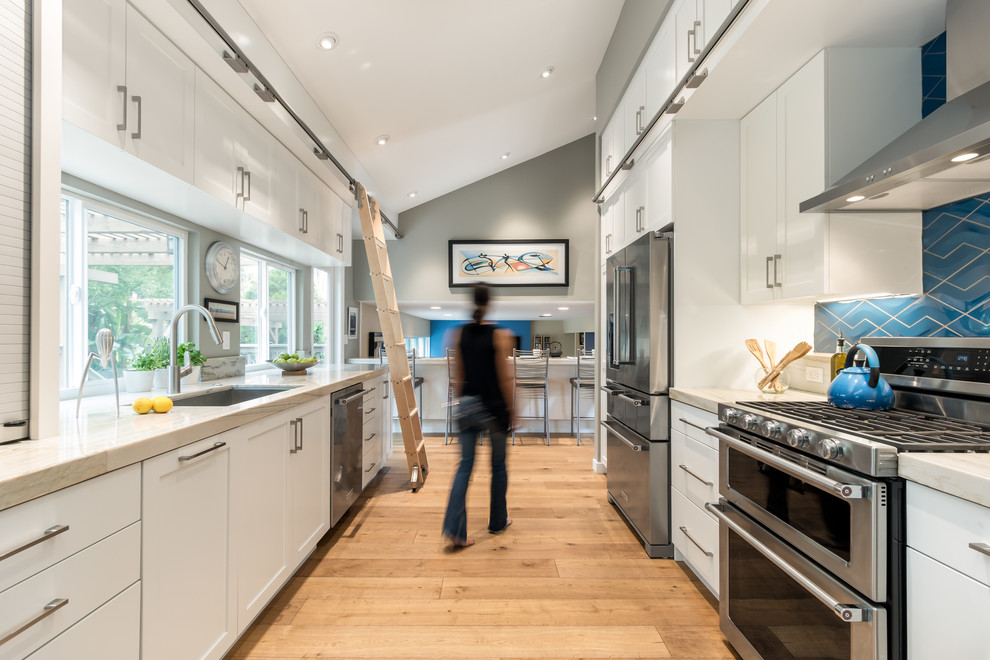 Eat-in kitchen - mid-sized transitional galley medium tone wood floor eat-in kitchen idea in San Diego with an undermount sink, shaker cabinets, white cabinets, quartzite countertops, blue backsplash, porcelain backsplash, stainless steel appliances and no island